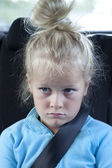 Grumpy kid with seatbelt in car — Stock Photo