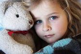 Sick little girl with teddybear — Stock Photo