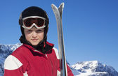Child with skis, helmet and goggles in the skiing slope — Stock Photo