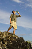 A Hiker Drinks Water on a Larger Boulder — Stock Photo