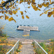 Stock Photo: Autumn on the River, boat and yellow foliage, footbridge