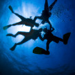 Four Scuba divers in silhouette connecting and forming a star underwater with sunburst on blue ocean surface. - Stock Photo