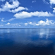 Infinite blue seascape with ocean horizon and white clouds — Stock Photo