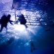 Scuba Divers in silhouet with sunburst climbing on to diveboat in the Similan Islands during a liveboard scuba diving trip in the Andaman Sea, Thailand. — Stock Photo