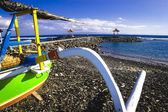 Traditional Balinese fishing boat painted green resting on the black stone beach in Candidasa on Bali's Northeast coastline in Indonesia — Stock Photo