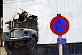 KUALA LUMPUR, MALAYSIA - SEPTEMBER 24: An old vehicle is breaking through a wall as store front decoration in Kuala Lumpur on September 24, 2010. Kuala Lumpur is a modern city popular for — Stock Photo