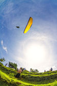Man flying off the grassy hills above Candidasa in Northeast Bali on October 1, 2010. The town of Candidasa is popular area for paragliding. — Stock Photo