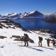 Snowboarders and skiers hiking up — Stock Photo