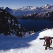 Snowboarder hiking up snow slope — Stock Photo