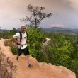 Stock Photo: Mhiking and running in mountains wearing white shirt and backpack