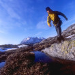 Young active couple hiking in the mountains of Greenland together wearing yellow and green jackets — Stock Photo