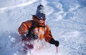 Etkin adam turuncu ceket dağlarda kayak toz kar kış — Stok fotoğraf