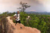 Man hiking and running in mountains wearing white shirt and backpack — Stock Photo