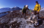 Young active couple hiking in the mountains of Greenland wearing yellow and green jackets — Stock Photo