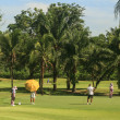 Golfers and caddies on golf course in Thailand - Stock Photo