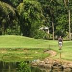 Senior golfspelare promenad med caddie till grön — Stockfoto