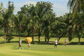 Golfers and caddies on golf course in Thailand — Stock Photo