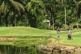 Senior golfer walking with caddie to green — Stock Photo