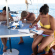 Stock Photo: Scubdiving students studying onboard dive boat