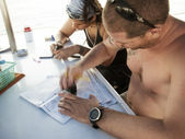 Dive instructor and student writing log books — Stock Photo