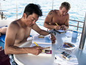 Scuba diving students studying onboard dive boat — Stock Photo