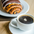 Chocolate bun with cup of coffee — Stock Photo