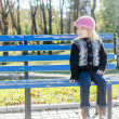 Little girl sitting on the bench at autumn park — Stock Photo