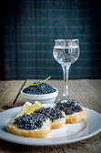 Sandwiches with black caviar and glass of vodka — Stock Photo