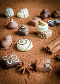 Luxury chocolate candies with cocoa background — Stock Photo