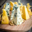 图库照片: Pieces of emmental and blue cheese