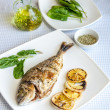Grilled dorada fish with lemon and spinach — Stock Photo