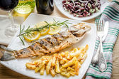 Baked seabass with fried potatoes — Stock Photo