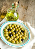 Olive oil and whole olives — Stock Photo
