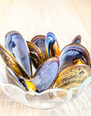 Bowl of mussels on the wooden table — Stock Photo