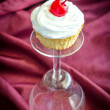 Cupcake with whipped cream and maraschino cherry — Stock Photo