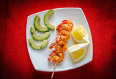 Shrimps skewers with avocado and lemon slices — Stock Photo