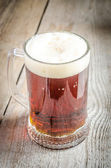 Mug with dark beer on the wooden table — Stock Photo
