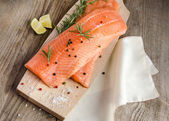 Raw salmon steaks on the wooden board — Stockfoto