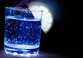 Glass with drink and lemon on black background — Stock Photo
