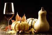 Pumpkins, red wine and autumn leaves — 图库照片