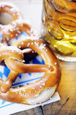 Pretzel and beer on bavarian napkin — Stock Photo