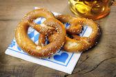 Pretzel and beer on bavarian napkin — Stock Photo