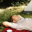 Stock Photo: Man resting on a blanket - camping serie