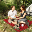 Couple dicussing hiking plans infront of a tent - camping serie — Stock Photo