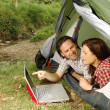 Couple with laptop - camping serie — Stock Photo