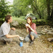 Stock Photo: Couple preparing food outdoors - camping serie