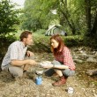 Couple preparing food outdoors - camping serie — Stock Photo