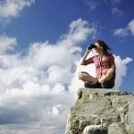Woman sitting on a mountain with binocular — Stock Photo #23867197
