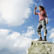 Woman standing on a mountain and gazing in the distance — Stock Photo #23867253