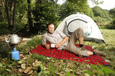 Camping serie: man resting in front of a tent — Stockfoto